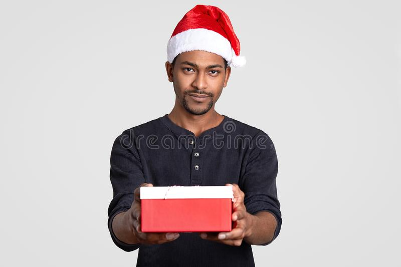 Isolated shot of serious black man wears Santa Claus headgear, carries little box of present, dressed in black jumper, poses over. White studio wall. People stock photo