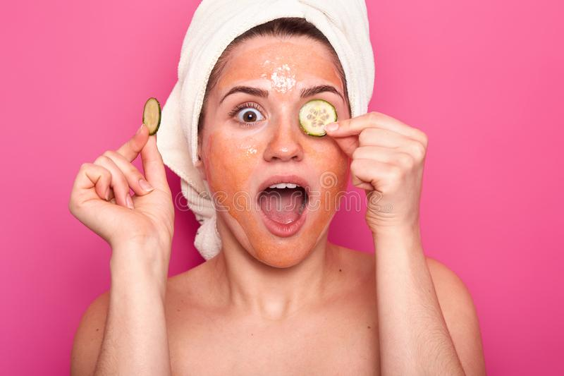 Isolated shot of surprised woman applies mask on face, slices of cucmbers on eyes, opens mouth fro amazement, shocked have no time. For beauty treatments, wears stock photo