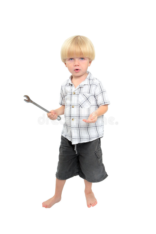 Isolated shot of young boy playing with large spanner stock image