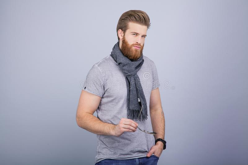 Isolated shot of young handsome male with beard, mustache and trendy hairdo, wears casual grey sweater, has serious stock photography