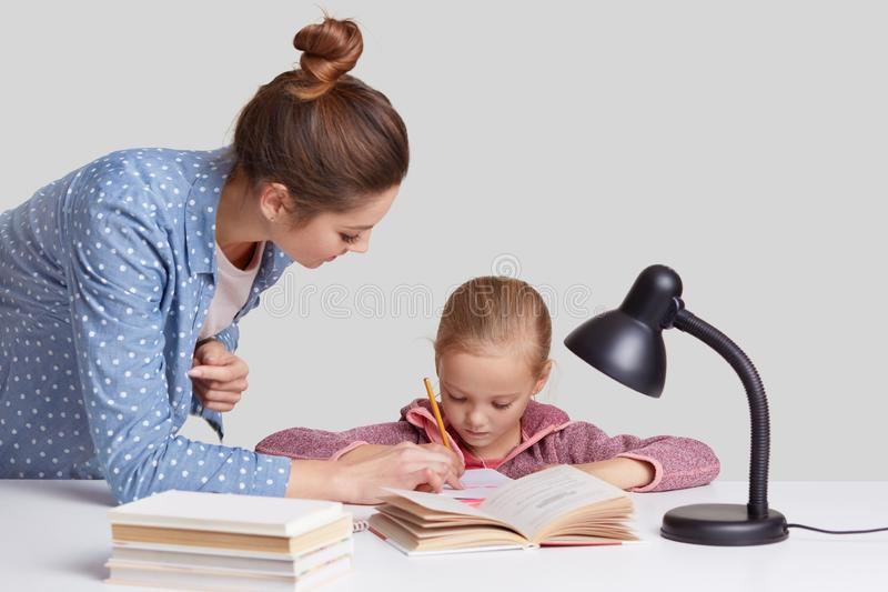Isolated shot of young mum in fashionable shirt helps to write her small daughter, read books, do homework together, use reading l royalty free stock images