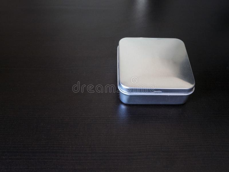 Isolated Plain rectangular tin canister on a dark background holding unknown contents version 2. Isolated Small Plain rectangular tin canister on a dark stock photography