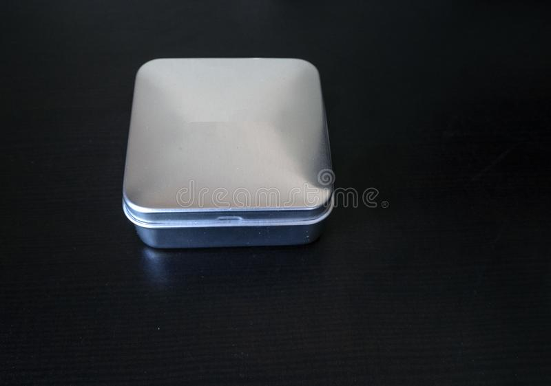 Isolated Plain rectangular tin cannister on a dark background holding unknown contents version 1. Isolated Small Plain rectangular tin cannister on a dark stock photos