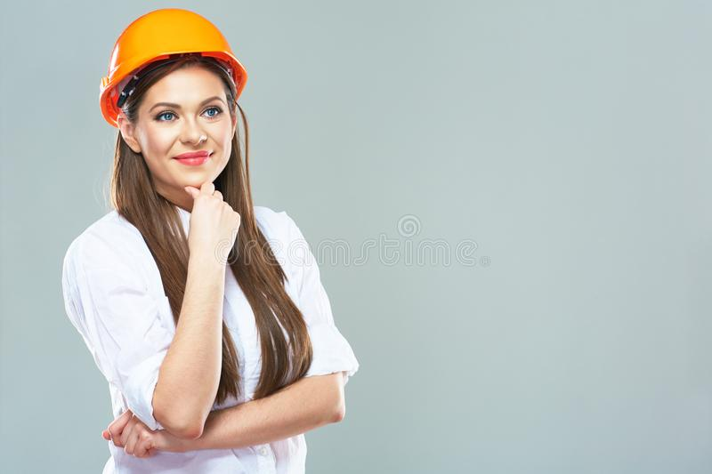 Isolated studio portrait of smiling woman manager of real estat. E. Business woman wearing protect helmet royalty free stock image