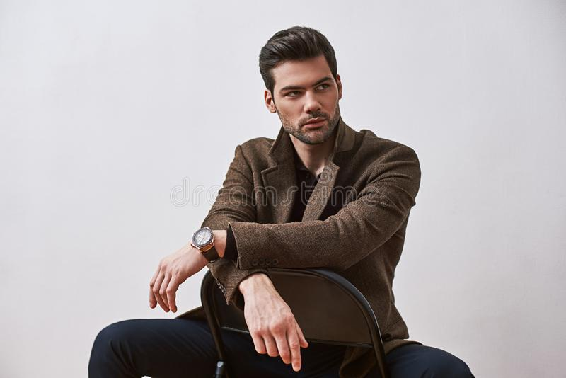 Perfect style. Stylish dark-haired man sitting on a chair and looking away isolated over white studio background stock images