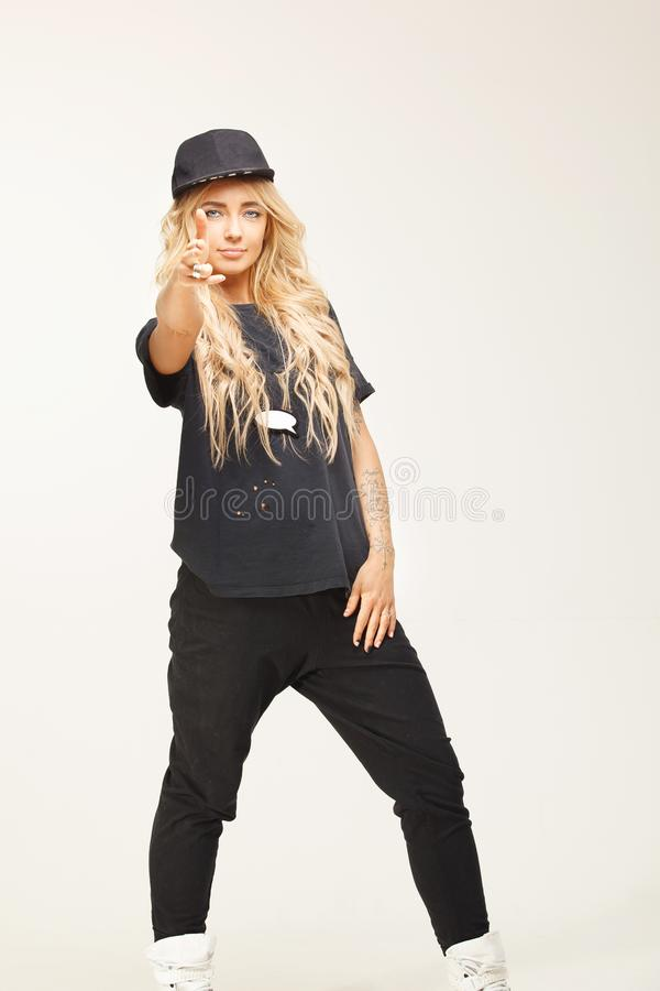 Isolated stylish blond woman in fashionable swag look gesture showing off with her fingers gun, pointing to camera. royalty free stock image