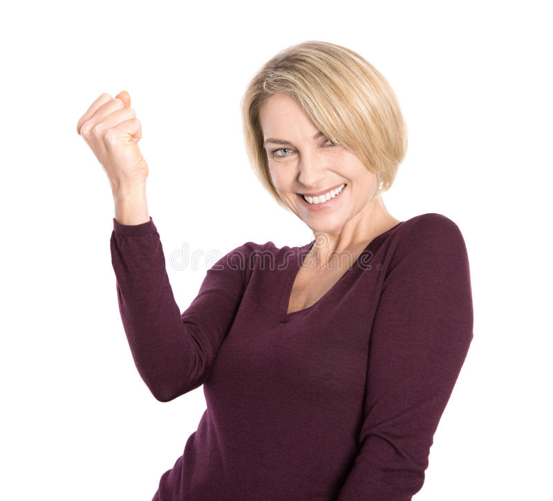 Isolated successful and happy older woman in pullover. Isolated successful and happy older woman in pullover making fist gesture royalty free stock photos