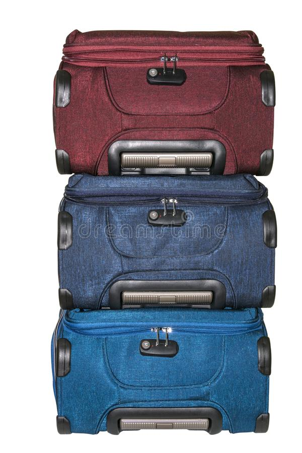 Isolated. Three large suitcases for travel lie on top of each other. Luggage with wheels. Green, blue and red suitcase close-up. royalty free stock photos