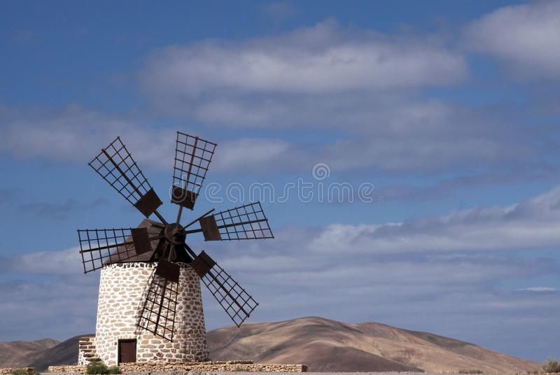 Isolated traditional windmill Molino de Tefia near La Olivia in dry arid hilly landscape against blue sky with cumulus clouds,. Isolated traditional windmill stock images