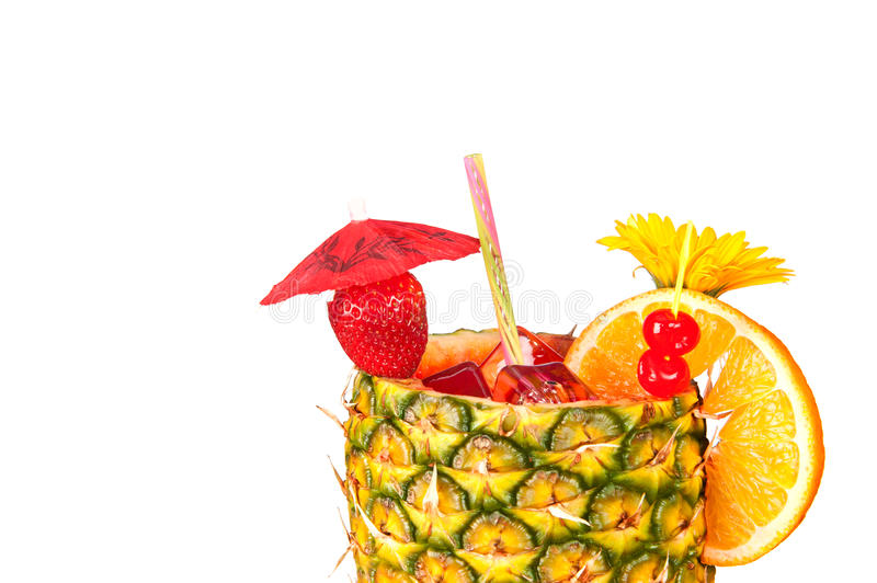 Isolated tropical drink. A cold, refreshing tropical rum drink with a pineapple glass, strawberry, cherries and an orange slice isolated on a white background stock images