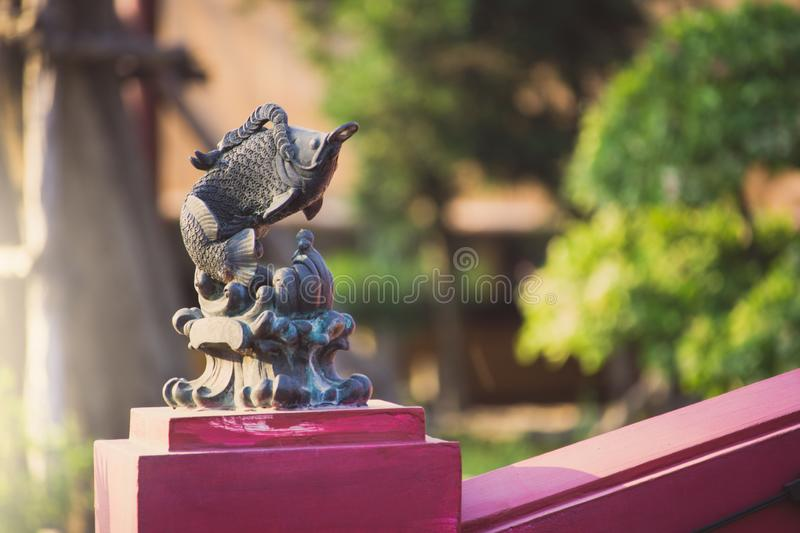 Isolated a vintage stone sculpture of a fish hold Chinese coins in mouth is decorated on a bridge in park. stock images