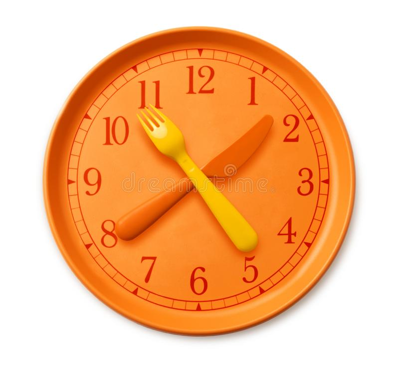 Isolated watch on the orange plate. Where instead of arrows yellow orange fork and knife. plastic utensils and clock on the table. concept of diet and health royalty free stock photography