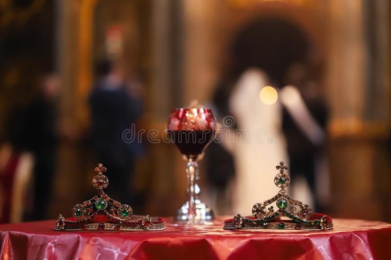 Isolated wedding crowns and blurred glass of vine in background. Orthodox church wedding accessories royalty free stock photos