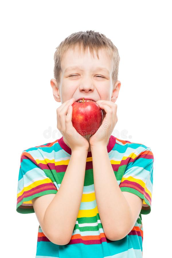 Isolated on white background portrait of a boy who eats. A red juicy apple stock image