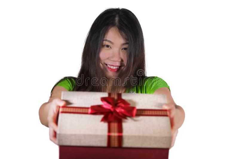 Isolated white background portrait of young happy and beautiful Asian Chinese woman showing gift box giving or receiving a birthda stock photo