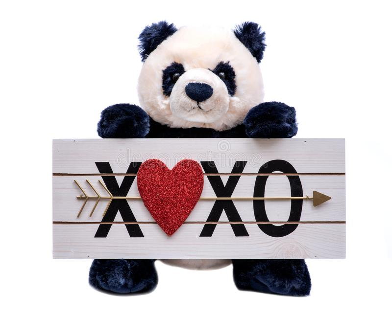 Isolated on white background stuffed plush Panda Bear toy is holding a Heart XOXO hugs and kisses wooden sign. royalty free stock image