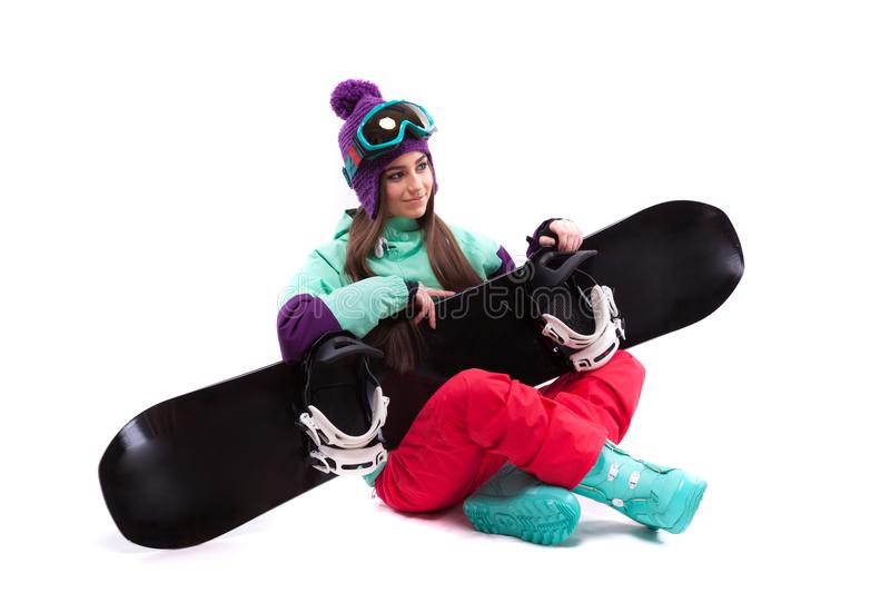 Pretty young woman in purple ski costume siting cross-legged royalty free stock image