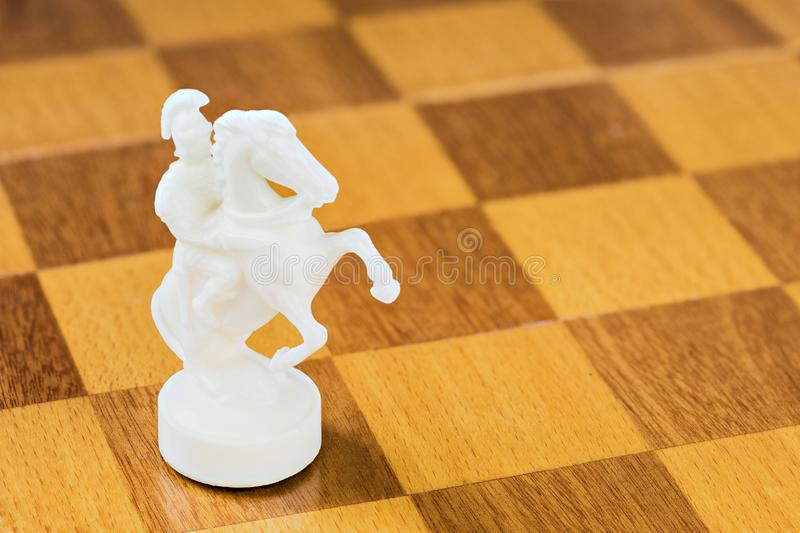 The isolated white chess knight of stone or plastic on the square wood board stock images