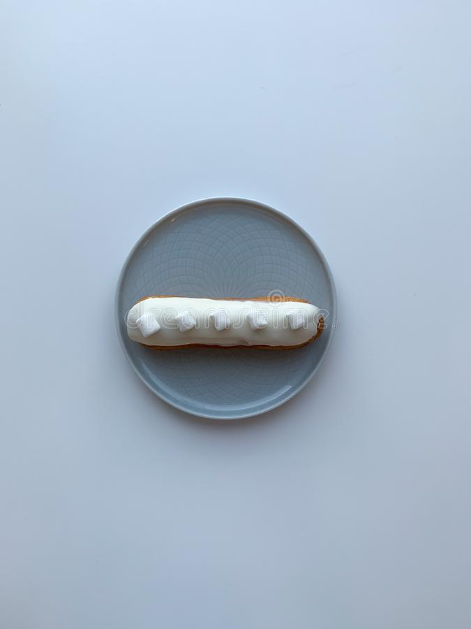 Isolated delicious white creme eclair with marshmallow on grey table. Dessert for breakfast and coffeetime. Top view. royalty free stock photo