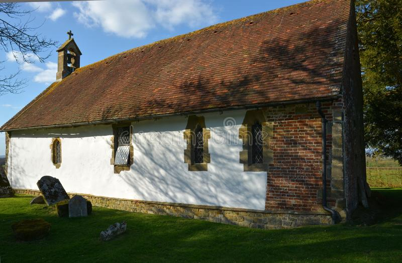 Ancient small church. St Andrews in Didling, Sussex, UK. The isolated whitewashed 13th century church of St Andrews is situated half a kilometre from the tiny royalty free stock images