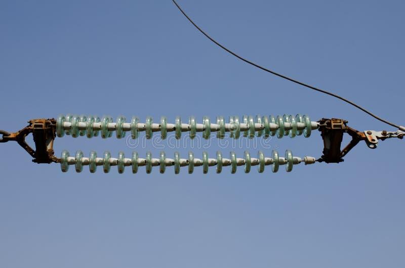 Isolateurs à haute tension de transmission contre le ciel bleu images stock