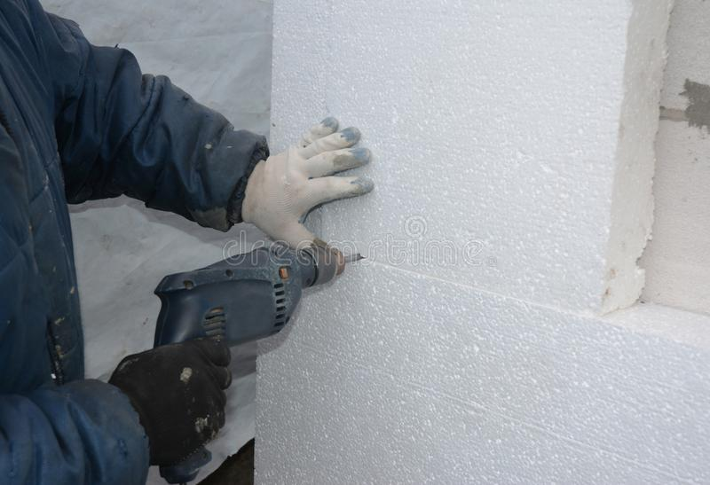 Isolation de mur Mur de perçage de constructeur pour installer des ancres pour tenir le panneau rigide de mousse d'isolation photos libres de droits