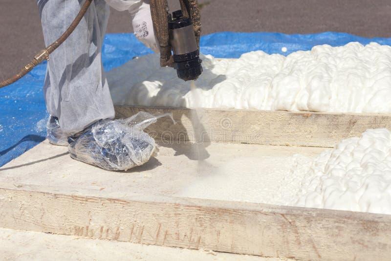 Isolation de pulvérisation de mousse de technicien utilisant le pistolet de pulvérisation composant pluriel image libre de droits