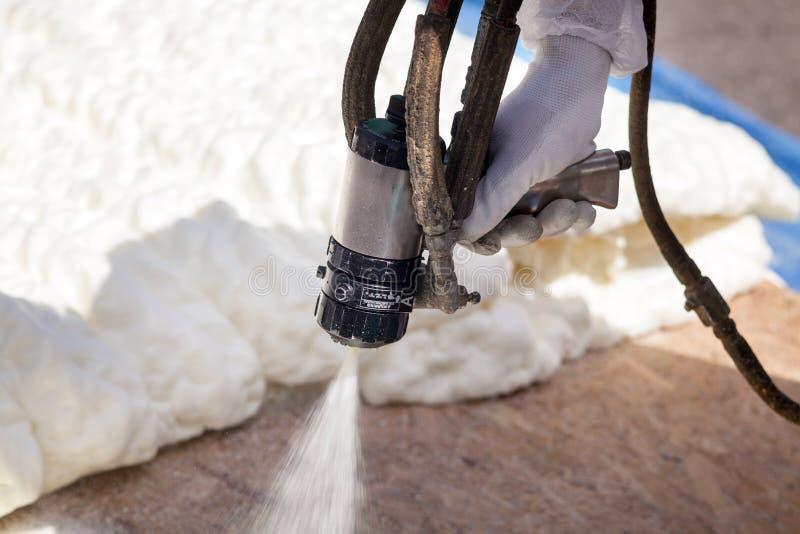 Isolation de pulvérisation de mousse de technicien utilisant le pistolet de pulvérisation composant pluriel photographie stock