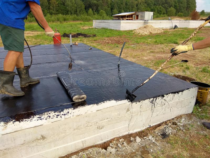 Isolation and waterproofing of the foundation of the building on the territory of the construction of the cottage stock images