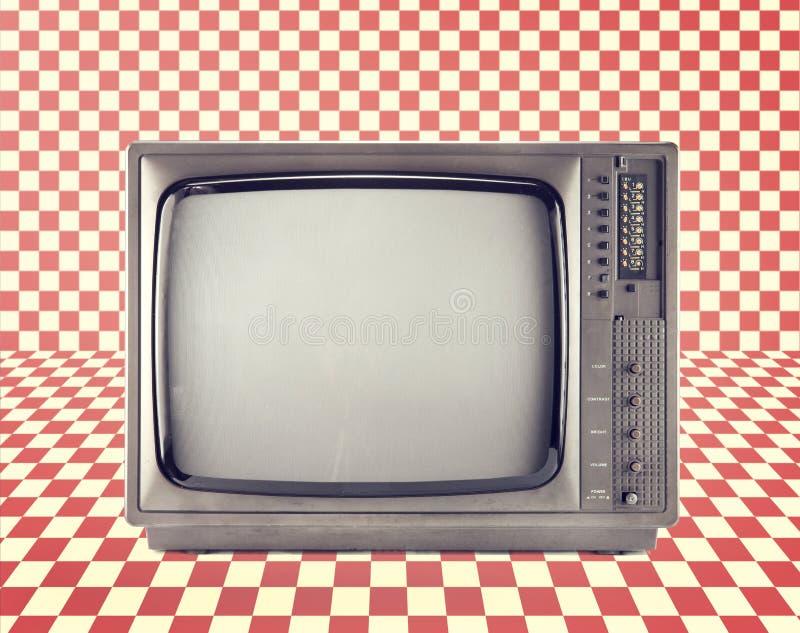 Isolato d'annata della televisione sul modello rosso della scacchiera, fotografie stock