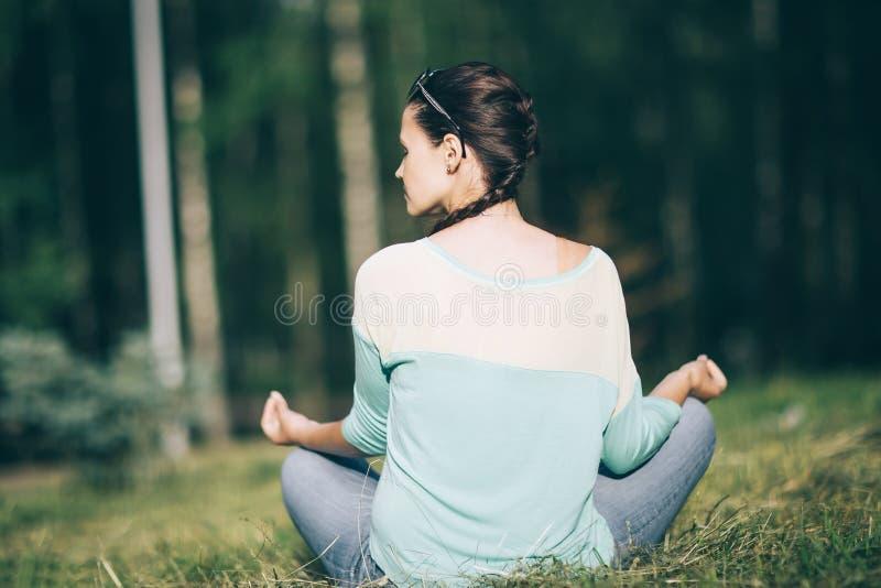 Isolato su bianco giovane donna che medita nella posizione di Lotus in Sunny Park fotografia stock libera da diritti