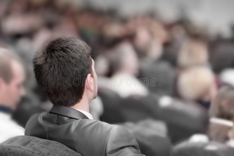 Isolato su bianco la gente di affari ascolta la conferenza nell'auditorium fotografie stock