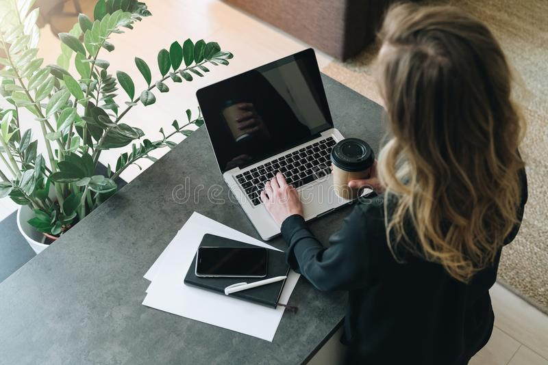 Isolato su bianco La giovane donna di affari è tavola vicina diritta, funzionamento sul computer portatile Vendita online, istruz fotografia stock libera da diritti