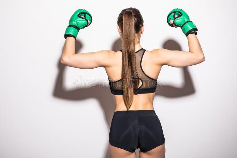 Isolato su bianco Ritratto donna sicura dell'atleta del lato posteriore di giovane che posa nell'inscatolamento dei guanti verdi  fotografia stock libera da diritti