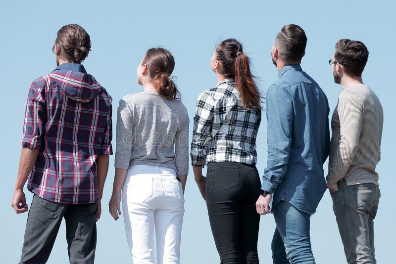 Isolato su bianco un gruppo di giovani che esaminano lo spazio della copia immagini stock libere da diritti