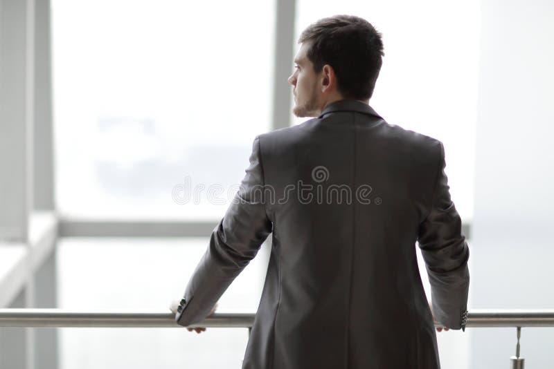Isolato su bianco uomo d'affari nell'abbigliamento casual che sta e che pensa vicino alla finestra dell'ufficio immagini stock libere da diritti