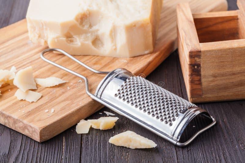 Isolato su fondo bianco Parmigiano e Olive Wood Parmesan Cheese Grater grattati fotografia stock libera da diritti