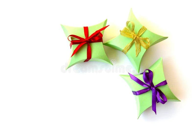 Isolato tre contenitori di regalo di carta verde mela con gli archi rossi, viola, dorati dei nastri del raso su fondo bianco con  immagine stock
