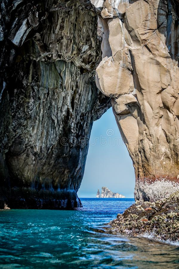 Isole dell'estrattore a scatto viste attraverso arco roccioso in Galapagos immagini stock libere da diritti