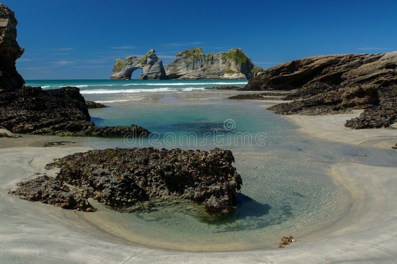 Isole della spiaggia & dell'arco di Wharariki in Nuova Zelanda fotografie stock libere da diritti