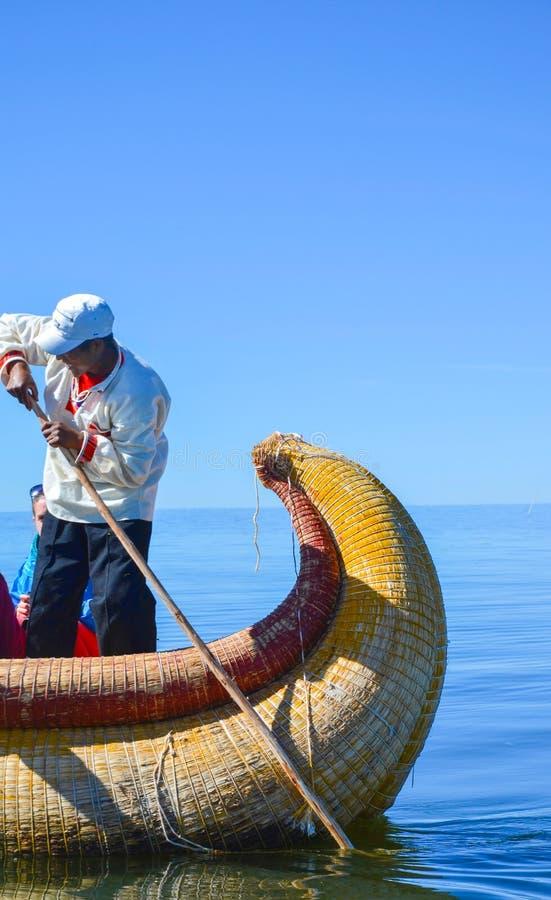 ISOLE DI GALLEGGIAMENTO DI UROS, PUNO, PERÙ 31 MAGGIO 2013: Uomo indigeno non identificato in una barca tradizionale sul lago Tit fotografie stock