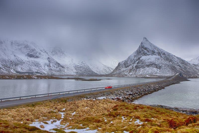 Isole di Lofoten in Norvegia Automobile notevole rossa che passa dal ponte di Fredvang alle isole di Lofoten nell'orario invernal immagine stock