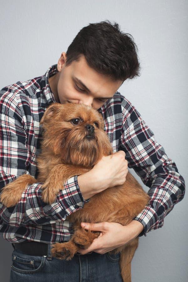 Isoleerde de knappe jonge hipstermens van het close-upportret, die zijn goede vrienden rode hond kussen lichte achtergrond Positi stock afbeeldingen