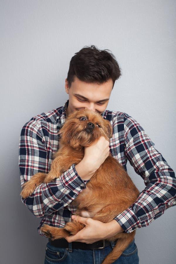 Isoleerde de knappe jonge hipstermens van het close-upportret, die zijn goede vrienden rode hond kussen lichte achtergrond Positi stock foto's