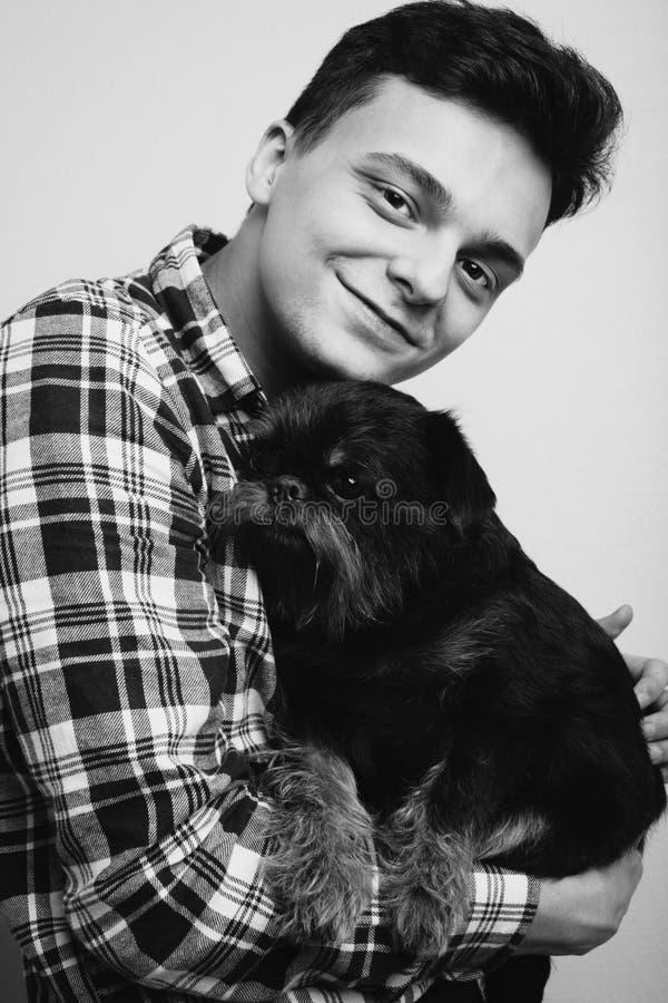 Isoleerde de knappe jonge hipstermens van het close-upportret, die zijn goede vrienden zwarte hond kussen lichte achtergrond Posi stock afbeeldingen