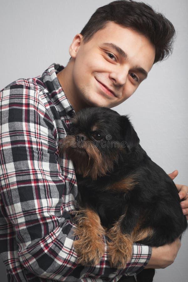 Isoleerde de knappe jonge hipstermens van het close-upportret, die zijn goede vrienden zwarte hond kussen lichte achtergrond Posi royalty-vrije stock fotografie