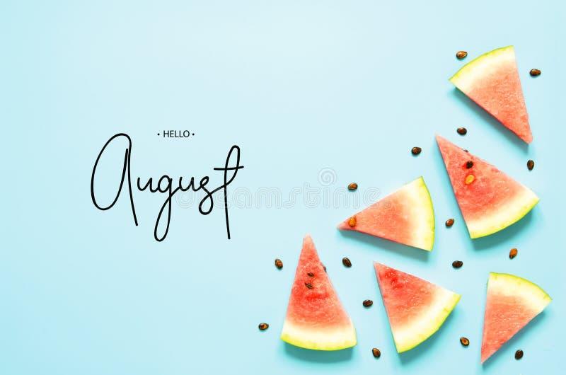 Isoleerde de rode de watermeloenplak van inschrijvingshello August Fresh lichtblauwe achtergrond De hoogste vlakke mening, legt stock afbeelding