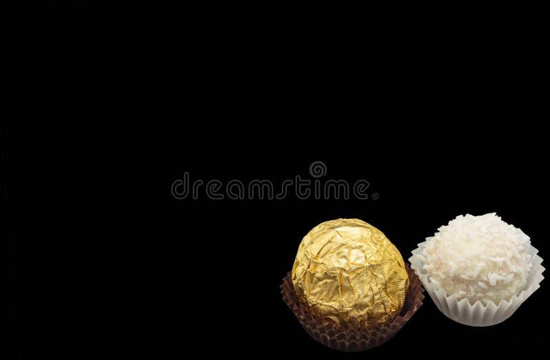 Isoleert de suikergoed zoete witte room met kokosnoot op een zwarte achtergrond gouden noot stock foto's