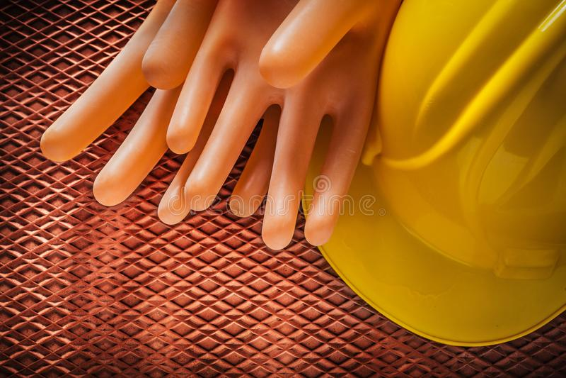 Isolera handskar som bygger hjälmen på dielectric rubber mattt arkivbilder