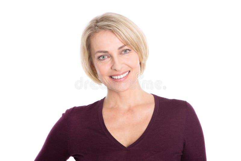 Isolerad äldre kvinna med blont hår - relaxt och le. royaltyfri fotografi